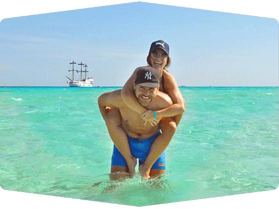Alex und Karo im Meer mit Segelschiff im Hintergrund