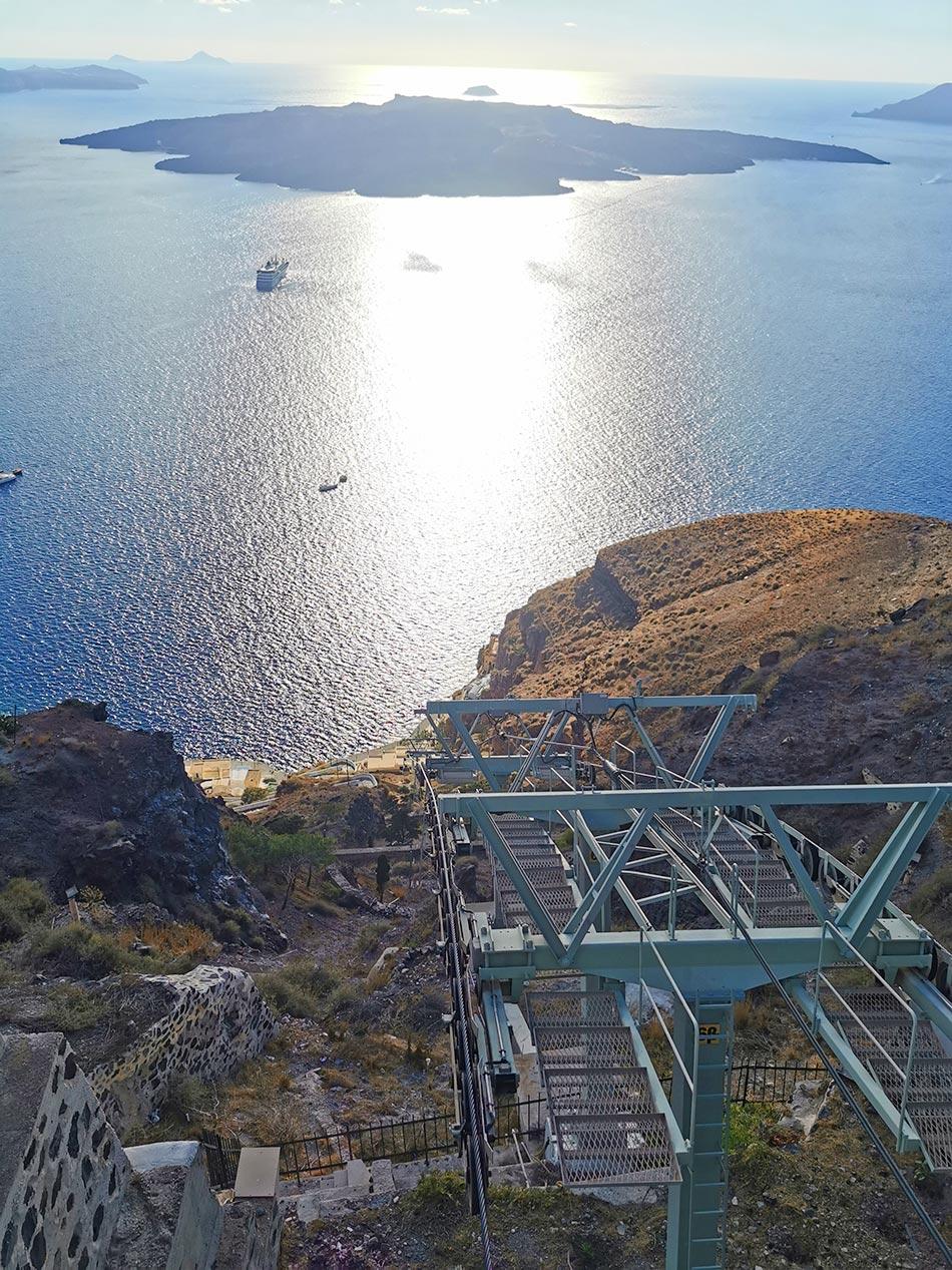 Santorini Sehenswürdigkeiten - Seilbahn Blick aus dem Fenster bei Sonnenuntergang über das Meer bis nach Neo Kamini