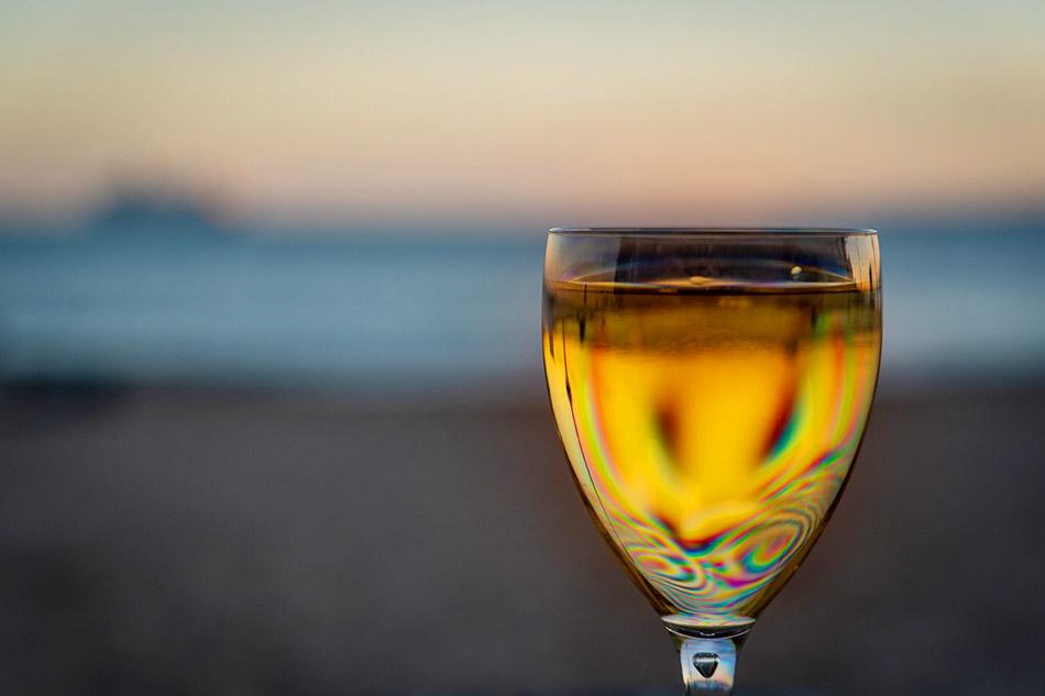 Paros Sehenswürdigkeiten - Paros Weisswein mit gekühlten Glas und Sonnenuntergang im Hintergrund