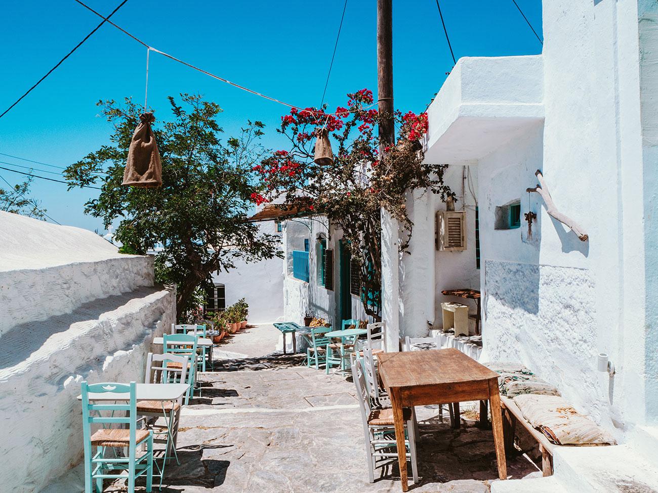 Chora Big Blue - Alte Gasse mit typisch griechischen Stühlen und einer Taverne
